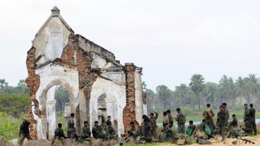 Sri Lankan soldiers beside the destroyed former headquarters of the Tamil Tigers in Mullaittivu.