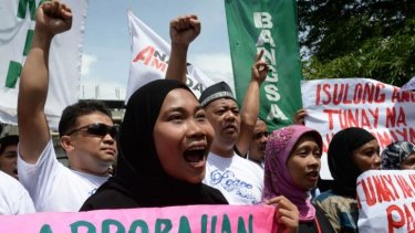 Filipino Muslims shout slogans in support of the passage of a law giving autonomy to minority Muslims.