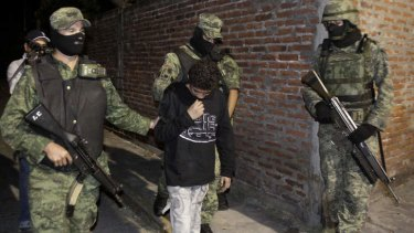 "Child killer ... Mexican soldiers with Edgar ""El Ponchis"" Jimenez Lugo in the city of Cuernavaca, Mexico after his arrest in 2010."