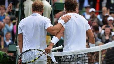 Historic win Steve Darcis walks off court with Rafael Nadal.