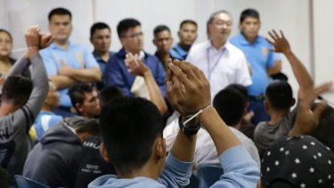 Men suspected to be Islamist militants raise their zip-tied hands, as they arrive at the Department of Justice in Manila>