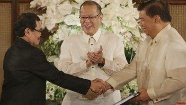 Philippine President Benigno Aquino (centre), with Moro Islamic Liberation Front chief negotiator Mohagher Iqbal (left) and Senate President Franklin Drilon.