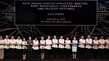Foreign ministers from Southeast Asia and their dialogue partners link arms during the gala dinner of ASEAN foreign ministers' meeting  in the  Philippines on Sunday.