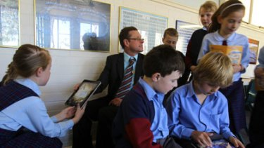 """""""I get my best writing from students this way"""" ... Tim Butt with pupils at St Finbar's Primary School. The class is trialling iPads."""