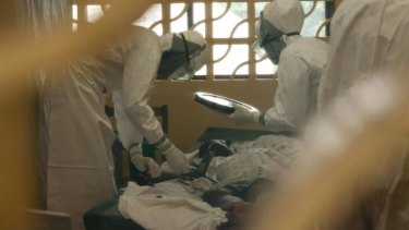 Dr Kent Brantly, left, at work with an Ebola patient in Monrovia, Liberia.