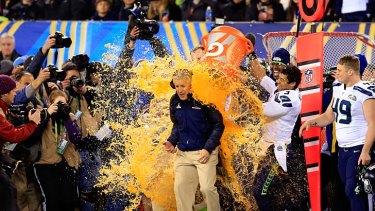 Tight end Zach Miller and quarterback Russell Wilson dump Gatorade on head coach Pete Carroll.