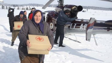 Bosnian people caring food supplies in a remote village, cut of by road due high snow fall.