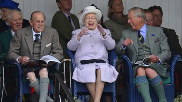 Highland tradition: At least the Queen and Prince Charles are amused by the weekend Braemar Gathering's sack race in chilly Scotland.