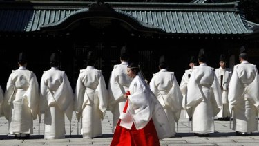 Controversial: A shrine maiden walks behind Shinto priests before a ritual to cleanse themselves at the Yasukuni Shrine during the Annual Autumn Festival in Tokyo on October 17.