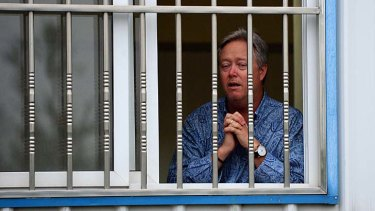 Praying for release: Chip Starnes stands behind a barred window at his Beijing medical supplies factory, after being held hostage for five days.
