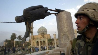 A US soldier watches as a statue of Iraq's President Saddam Hussein falls in central Baghdad April 9, 2003.