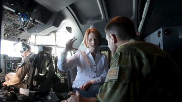 Prime Minister Julia Gillard is briefed by Major-General Angus Campbell (right), Commander of Joint Task Force 633, in the cockpit of a C-130 aircraft during her visit to Afghanistan yesterday.
