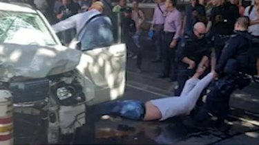 A man is dragged from a car in Flinders Street after an attack that left 18 people injured.