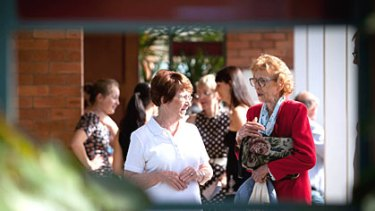 Parishioners mingle after a service at St Mary's Catholic Church in Gatton almost a week after the devastating flood.