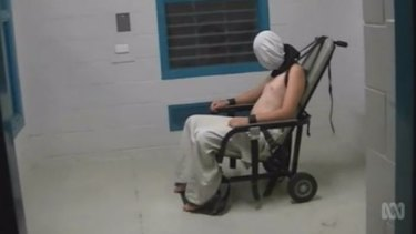 A teenage Dylan Voller has a hood placed over his head and is strapped to a chair at the Don Dale Detention Centre.