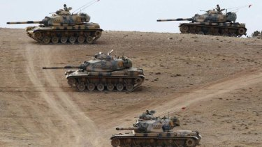 Turkish army tanks take up position on the Turkish-Syrian border.