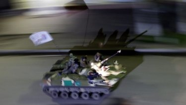 Pro-Russian gunmen atop an armoured personal carrier patrol through the centre of Slaviansk.