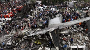 Security forces and rescue teams examine the wreckage of an Indonesian military C-130 Hercules transport plane.