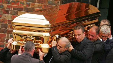 The gold coffin containing convicted drug trafficker and murderer Carl Williams is carried by pallbearers at his funeral in April 2010.