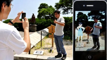A man stands next to a tiny black and white panel to have his picture taken and displayed including the animated image of a girl through an iPhone application at the famous spot of Kanichi and Omiya in Atami, southwest of Tokyo.