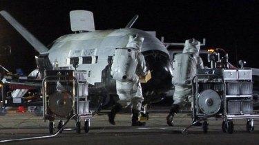 Technicians conduct post-landing checks on an earlier X-37B at Vandenberg Air Force Base in California.