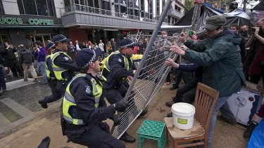 Police scuffle with protesters trying to barricade themselves inside the makeshift camp.