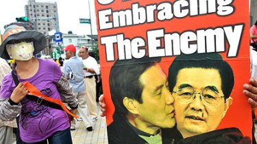 A protester holds a placard depicting Taiwan's President Ma Ying-jeou and Chinese President Hu Jintao during a protest last Saturday in Taipei.