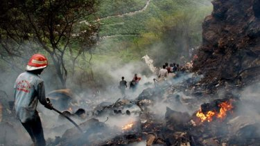Plane crash ... Pakistani rescue workers search the wreckage.