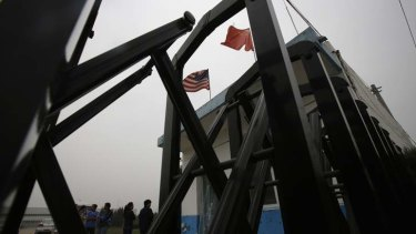 Flags belonging to the U.S. and China flutter through a closed gate at a factory where Chip Starnes, the co-owner, is being held hostage, on the outskirts of Beijing, June 25, 2013.