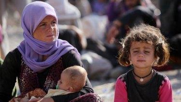 A Yazidi Iraqi woman sits with her children at the Bajid Kandala camp near the Tigris River in Kurdistan after fleeing advances by Islamic State jihadists in Iraq.