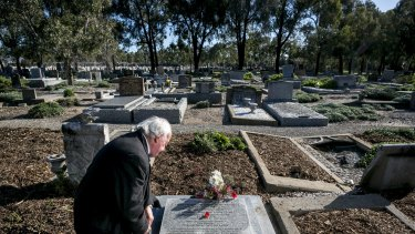 Anthony Hill, author of the new book Young Digger, pictured at Fawkner cemetery, Melbourne, at the grave of Henri Hemene Tovell, the French orphan smuggled from Europe by Australian airmen after World War I.