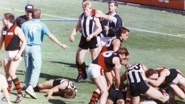 At quarter-time in the 1990 grand final, Collingwood's Gavin Brown is on the ground after being knocked out by Bomber Terry Daniher amid an all-in brawl.