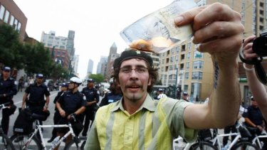 A man burns a Canadian five-dollar note during a protest at the G20 summit in Toronto.