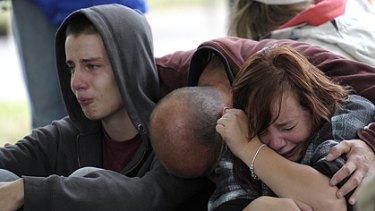 Kent Manning (left) and his sister Libby are comforted by their father after hearing there was no hope of finding their mother.