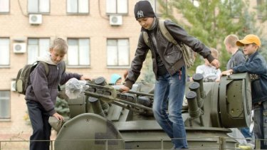 Child's play: With truce talking continuing, kids turn a silent tank into a playground in Soledar.