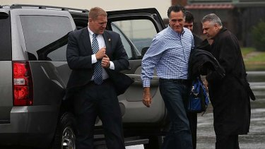 Secret Service agents look on as Republican presidential candidate Mitt Romney boards his campaign plane. In the wake of Hurricane Sandy, the campaign has reduced their schedule and is focusing on disaster relief.