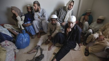 Students sit at a police station after being rescued.
