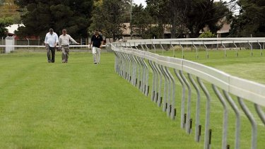Officials inspect the condition of the Werribee Racecourse track.