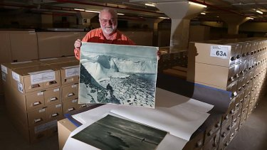 Visual DNA: Alan Davies at the State Library with a Frank Hurley photograph of Antarctica.