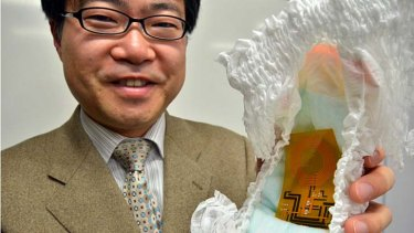 University of Tokyo professor Takao Somey holds a nappy containing the world's first flexible wireless organic sensor system.
