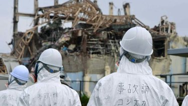 Disaster ... members of a Japanese government panel inspect the damaged building which housed reactor number three at Fukushima in June, 2011.