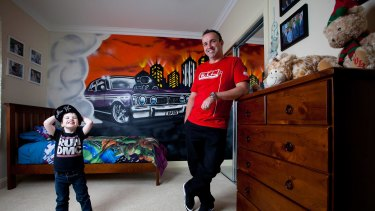 Commercial graffiti artist Ashley Goudie (right) in front of the GT Ford Falcon he spray painted in the bedroom of Braxton Vella, 3, (left) of Melton.