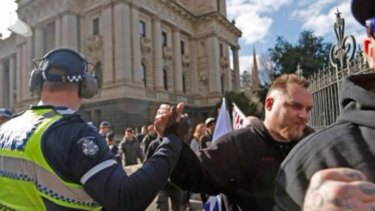 A Victoria Police officer appears to high-five a protester.