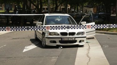 The BMW at the centre of a Sydney-wide police pursuit sits outside Surry Hills Police Station, its windscreen riddled with bullet holes.