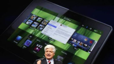 Mike Lazaridis, president and co-chief executive officer of Research in Motion, holds the new Blackberry PlayBook with a screen projection of the device as he speaks at the RIM Blackberry developers conference in San Francisco, California.
