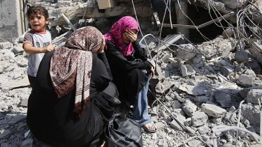 Palestinian women sit on the rubble of their home in Beit Hanoun.