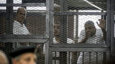 Peter Greste (left) and his colleagues Mohamed Fadel Fahmy and Baher Mohamed listen to the verdict from inside the defendants' cage.