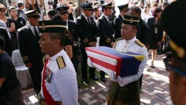 Malaysian Army soldiers carry an urn containing ashes of pilot Eugene Choo of Flight MH17 shot down over eastern Ukraine in July, at his home in Seremban, Malaysia.