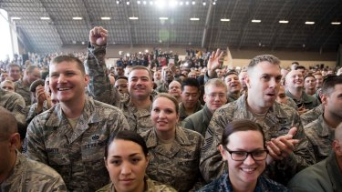 Members of the audience watch as the president speaks at a hanger rally at Yokota Air Base.