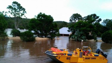An SES crew rescues a family from a flooded home at Luscombe before it is swept away.
